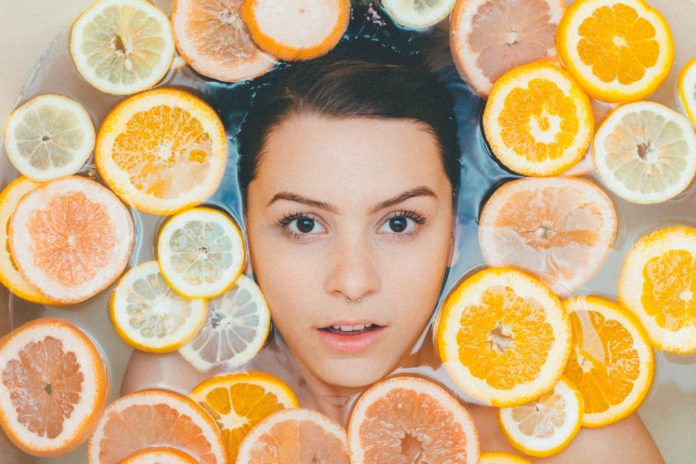 beautiful woman soaked in citrus infused water for glowing skin